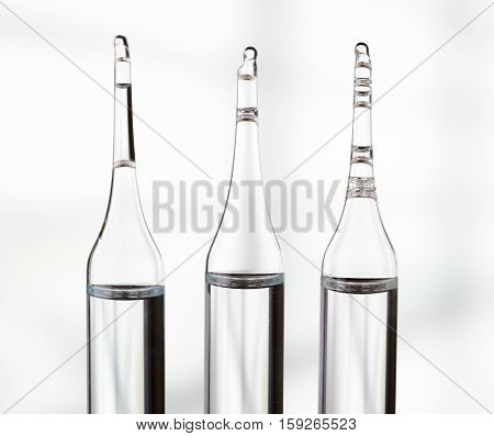 Three Ampoules On Light Background