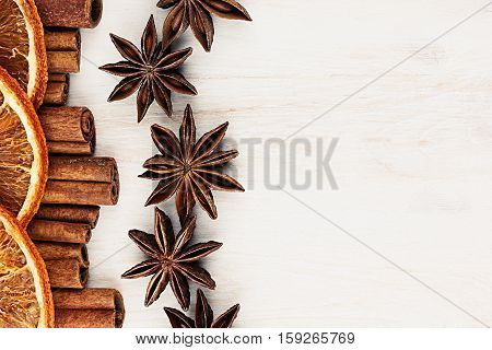 Cinnamon sticks anise star and oranges closeup on white wood background. Christmas decorative border of cinnamon sticks spice. Top view.