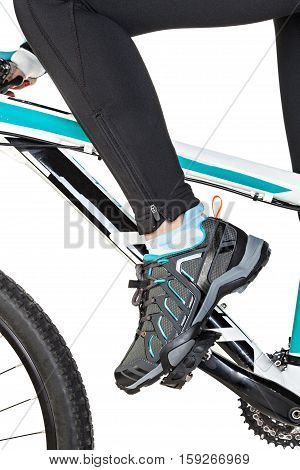 Close Up of the female leg in special contact shoe attached to the bicycle pedal.
