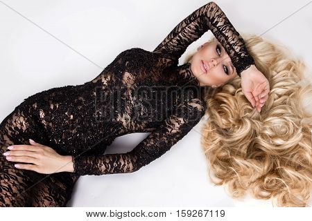 Portrait of beautiful sexy young woman model with long blond hair volume amazing eyes dressed in long lace dresses elegant makeup of a flirtatious smile