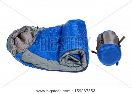 Two of the same sleeping bags in a compression bags and unpacked isolated on white background. Studio shot.