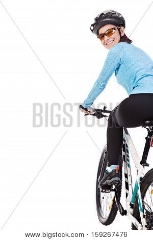 Adult woman cyclist riding a bicycle looks back and smiling isolated on white background. Studio shot.