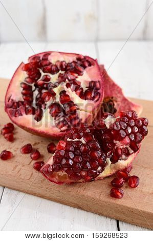 Ripe garnet have broken into pieces on a white background. Juicy Asian fruit. Close up.