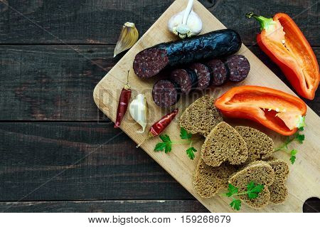 Morcillo (Spanish black pudding blood sausage) cutting slices black rye bread in a heart shape pepper garlic on a wooden board. The top view on a dark background. A festive meal on Christmas Easter