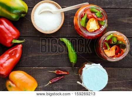 Marinated vegetables in a jar of glass: hot red and green peppers with sugar. The top view