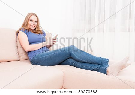 Pretty Lady Sitting On Couch Holding Smartphone