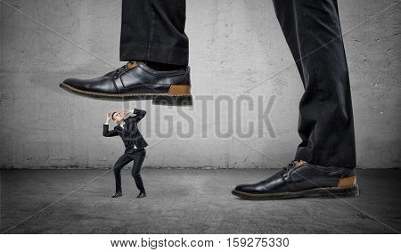 A tiny frightened man under a feet of a huge businessman on grey wall background. Chiefs pressure. Stress on work. Business ranking.
