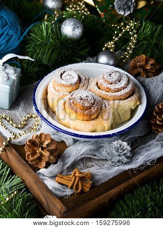 Cinnamon Roll Buns In Bowl With Christmas Baubles. Vertical