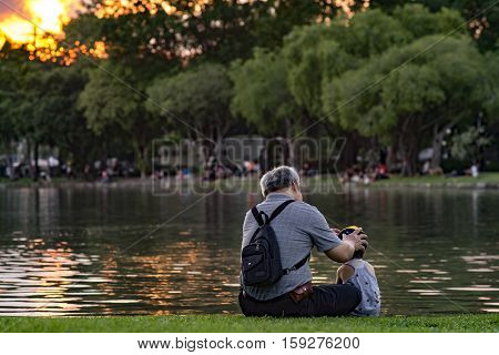 Grandpa And Nephew Relaxing In Chatuchak Park