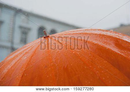 rain drops falling from a orange umbrella