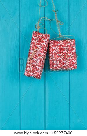 Christmas background of red apresents Christmas decorations hanging on rope in front of blue wooden background.