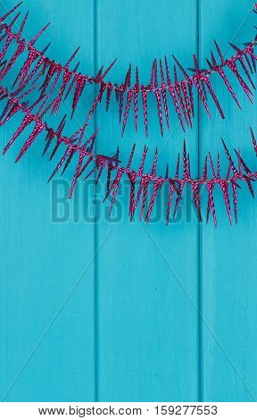 Purple Christmas tree garland on blue wooden background