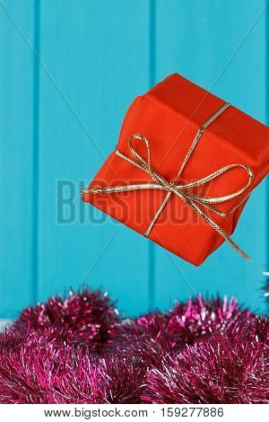 Gift box with dots floating in the air over blue background with copy space