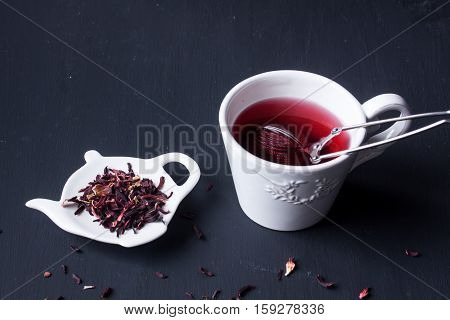 a cup of hibiscus herbal tea on a black background