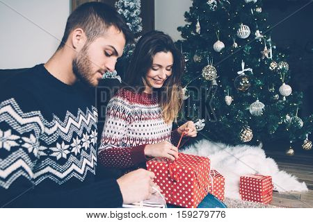 Young couple wearing sweaters sitting on sofa and unwrapping presents with Christmas fir tree on background.