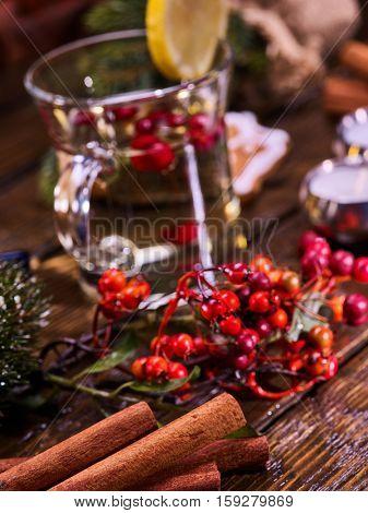 Christmas background with mug decoration lemon slice hot drink . Cinnamon sticks in foreground. Sharpness is on cinnamon sticks.