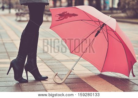 Umbrella and femail black boots on the wet street (vintage)
