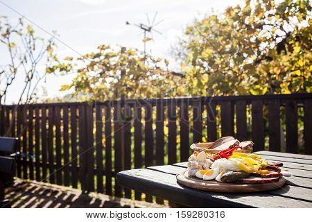Brettljause traditional wooden plate with cold cuts only with self-made food on terrace in vineyard on western Styria vine route