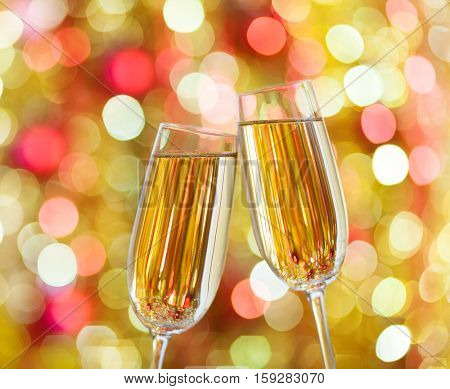 Two glasses of champagne against background with sparkles. Very shallow depth of field. Selective focus