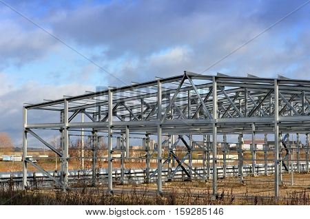 Metal frame of an industrial building warehouse in the construction process in perspective.