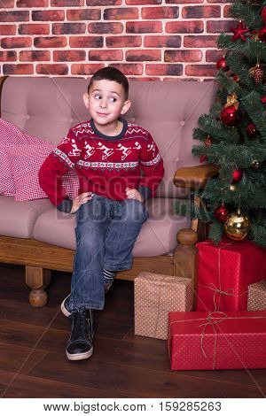 The boy sits in a chair and smiling