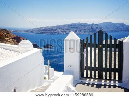 blue gates against volcano caldera and Aegan sea, beautiful details of Santorini island, Greece, retro toned