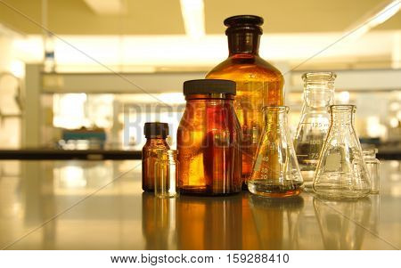 glass flask and retro brown bottle reagent in research lab science