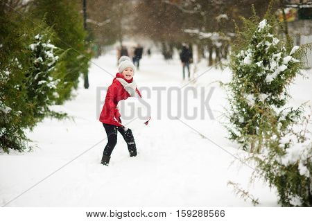 Cheerful girl of younger school age builds snowman. She holds a huge snow sphere in hand and laughs. It is snowing. All ground in park is covered with snow. Girl in bright red jacket and knitted hat.
