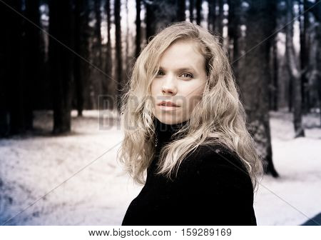 portrait of a woman with blond curly hair on the background of the winter forest, processed photo in shades of brown, bright woman with alluring and attractive look, languid, snowing,