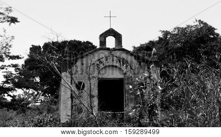 Old small chappel deteriorated by time surrounded by woods inspiring dark mood B&W