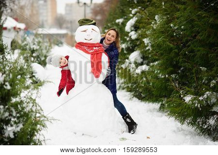 The young woman and her daughter look out because of a big snowman. In the park it is snowing. All earth is covered with fluffy snow. Mother and the daughter cheerfully spend time.