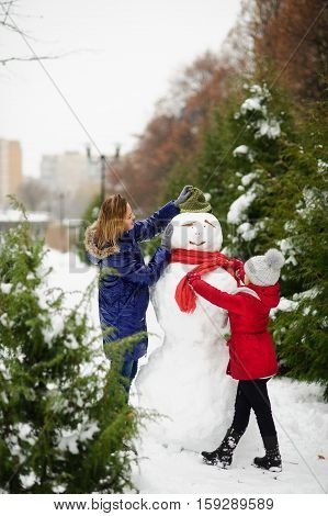 Mother with daughter of school age have built a snowman. Woman putting on his hat on the snowman. Girl tying his scarf. All ground in park is completely covered with fluffy snow.