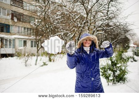 Young woman throws snowball. She aims in someone and laughs. She is dressed in a bright blue down-padded coat with a hood. It is snowing. Ground is covered with snowdrifts. Woman likes such weather.