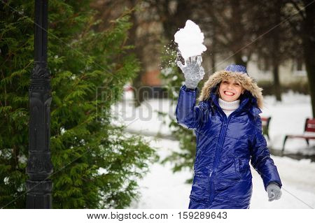 Cute girl throws snowball. She is dressed in a bright blue down-padded coat with a hood. It is snowing. Ground is covered with snowdrifts. She aims in someone. Girl has an good mood. She laughs.