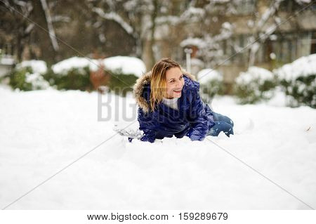 White Christmas. Cheerful young woman lies on snow and holds a snowball in hand. The woman without headdress. It is snowing. All ground in the park is covered with snow.