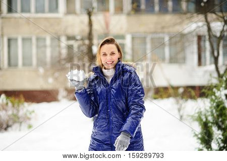 Beautiful young woman plays snowballs. It is snowing. Earth is covered with snowdrifts. Woman is dressed in a bright blue down-padded coat without headdress. Excited by play she does not feel cold.