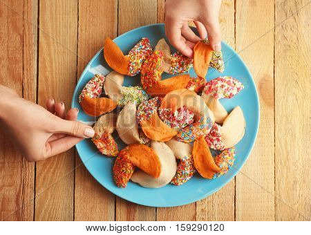 Hands taking colorful fortune cookies from plate on wooden background