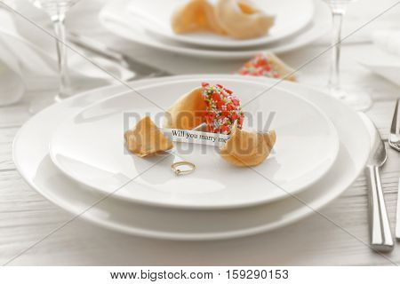Offer of marriage with fortune cookies and ring on white plate closeup
