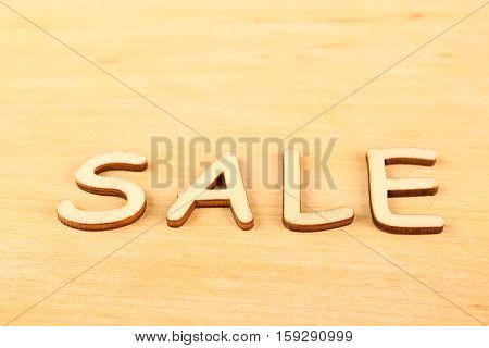 Close-up wooden letters sale on a wooden background