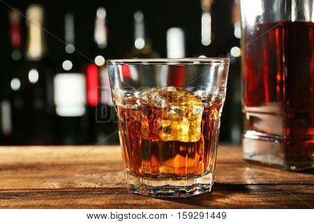 Glass of whisky on wooden bar closeup