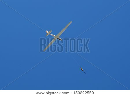 propeller-driven airplane is towing a glider in the sky
