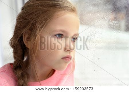 Close up view of little girl looking out of window