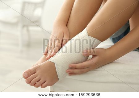 Little girl touching ankle with elastic bandage, close up view