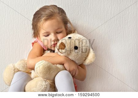 Sad little girl with teddy bear on light background