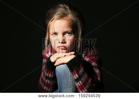 Disappointed little girl on black background
