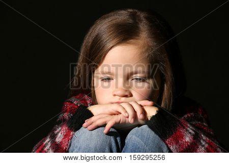 Sad little girl on black background, close up
