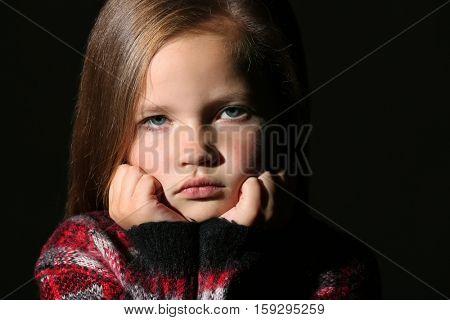 Portrait of cute little girl on black background