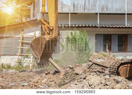 bucket Excavator. excavator destruction in work construction and dust soil motion with sunset light tone.