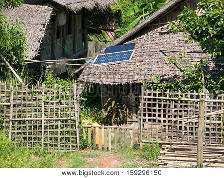 Straw house with solar panel on the roof in a village at the Rakhine State of Myanmar.
