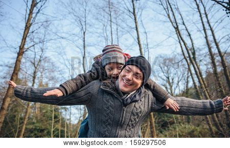 Portrait of happy man giving piggyback ride to smiling kid and raising their arms into the forest